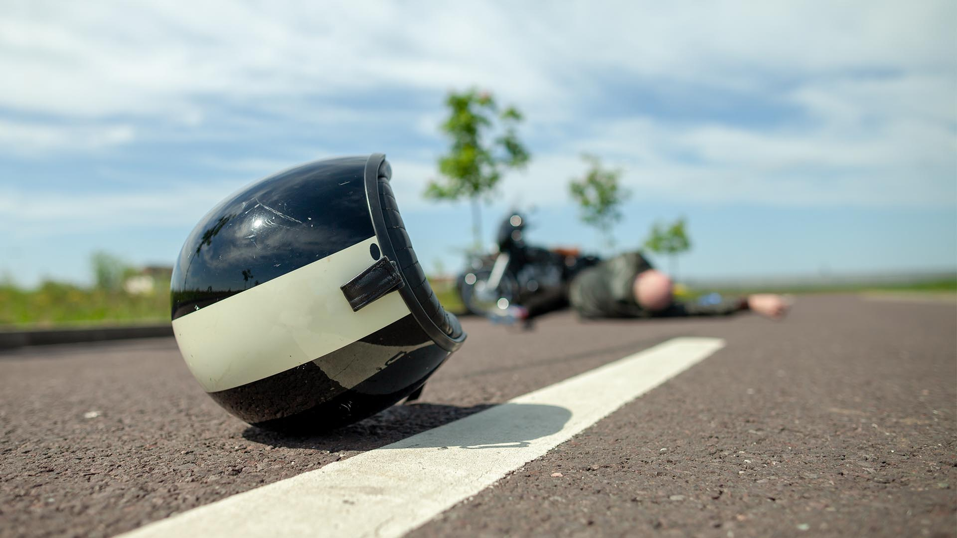 motorcycle helmet and rider lying on road