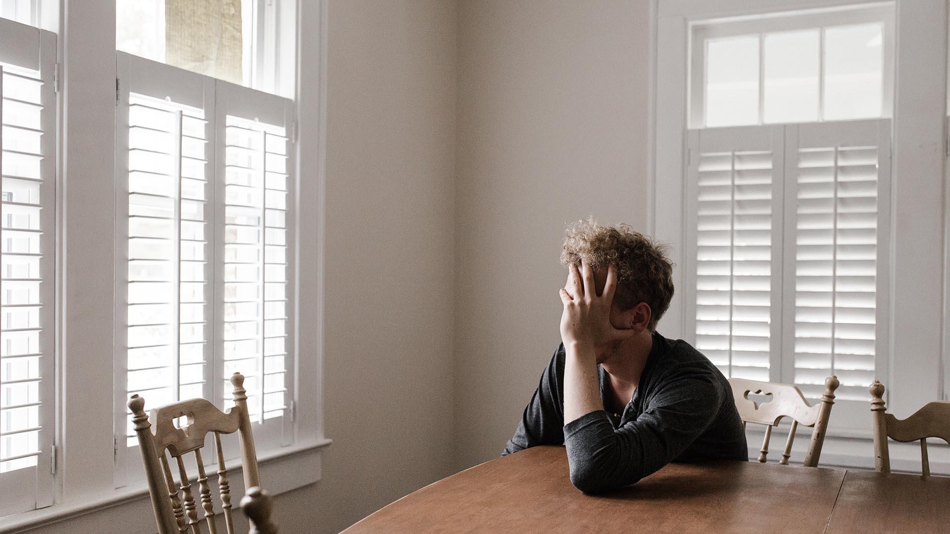 sad teenager at a kitchen table